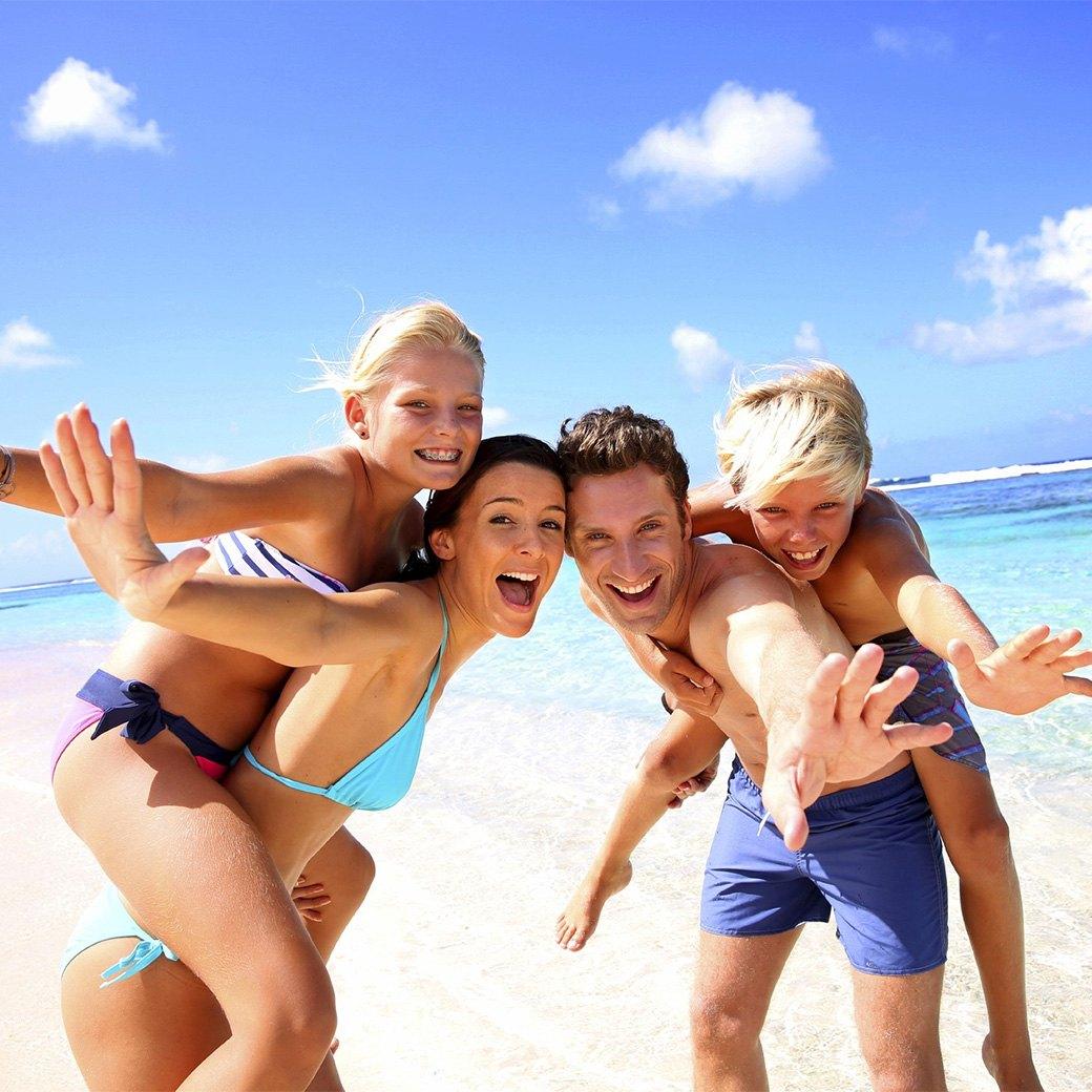 Счастливая семья из 4 человек на пляже